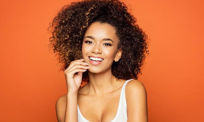 haarschnitt 2020, eine schöne frau mit afrolocken, blonde spitzen, oranger hintergrund, weißer top