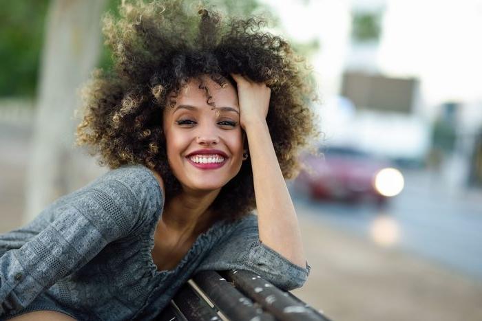 haarfarben trends 2019, afro locken mit blonden spirzen, lustige frau mit schönen haaren