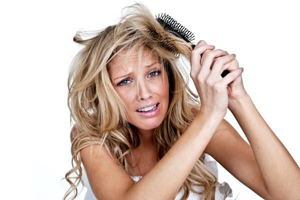 haartrends 2019, gesundes blondes haar pflegen, lochen in den haaren, eine frau versucht ihre haare zu kämmen