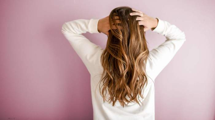 haarschnitt 2019, langes haar, eine frau trägt weißes oberteil, rosa wand dahinten