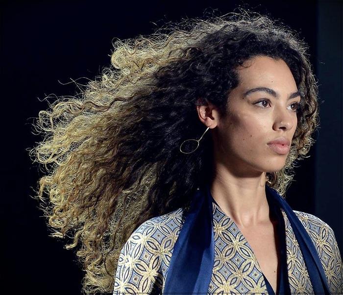 haar trend 2020, langes lockiges haar mit blonden spitzen, eine model geht auf der bühne beim schau