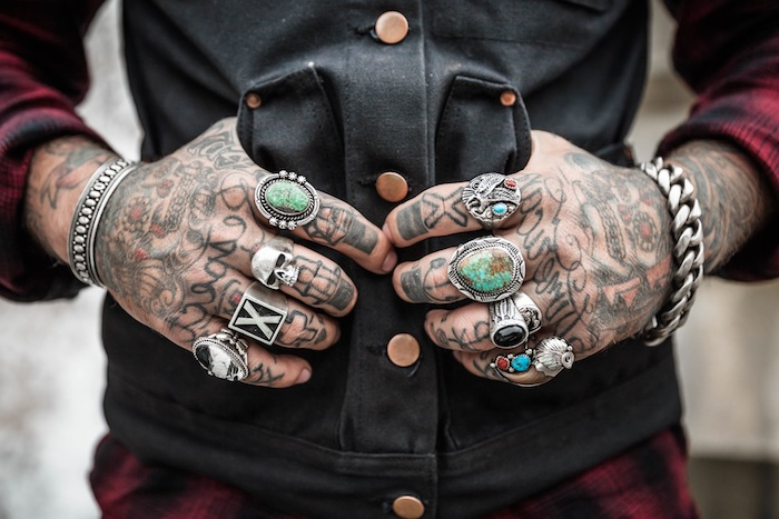 Viele Tattoos an der ganzen Hand, silberne Ringe mit Steinen an jedem Finger