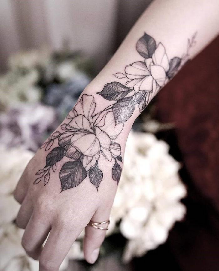 Blumen Tattoo an der Hand, zwei Ringe am Daumen, weibliche Tattoo Motive mit Bedeutung