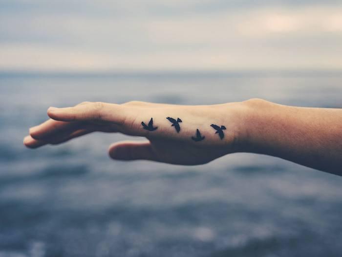 Vögel Tattoo an der Hand, vier kleine Vögel, Symbol der Freiheit, Motive für Hand Tattoos