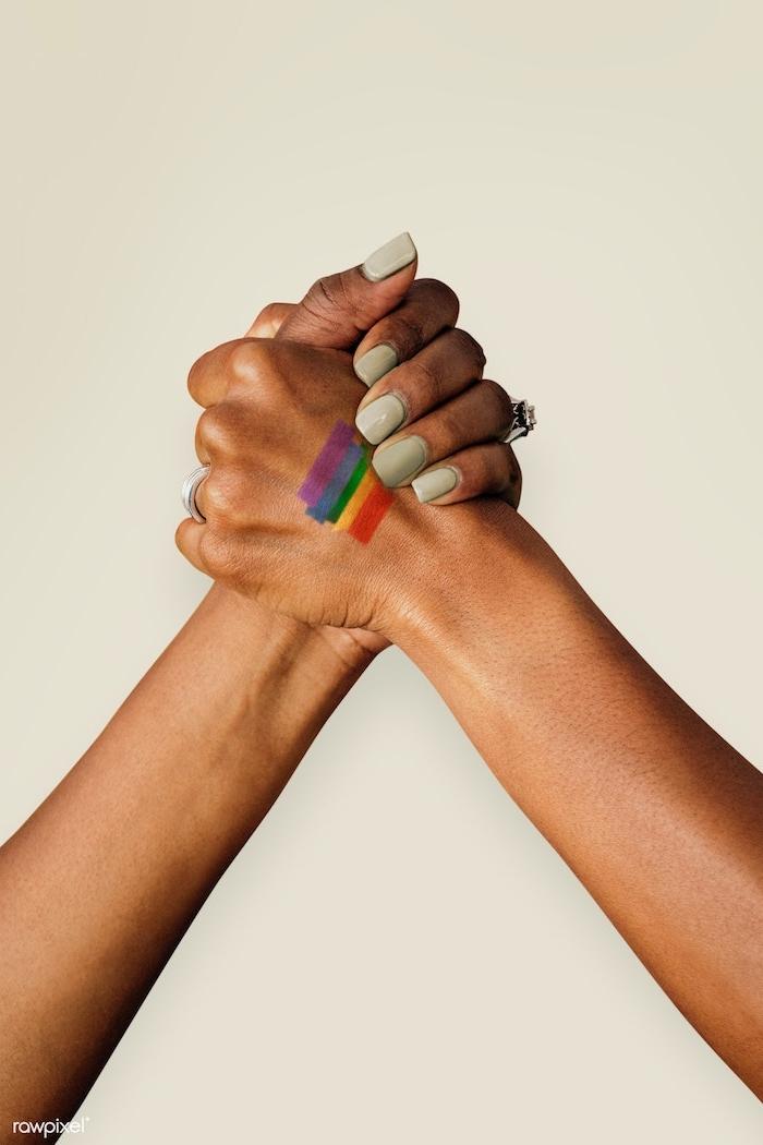 Regenbogenfahne Tattoo an der Hand, farbige Tattoo Motive, Nagellack in Pastellfarbe