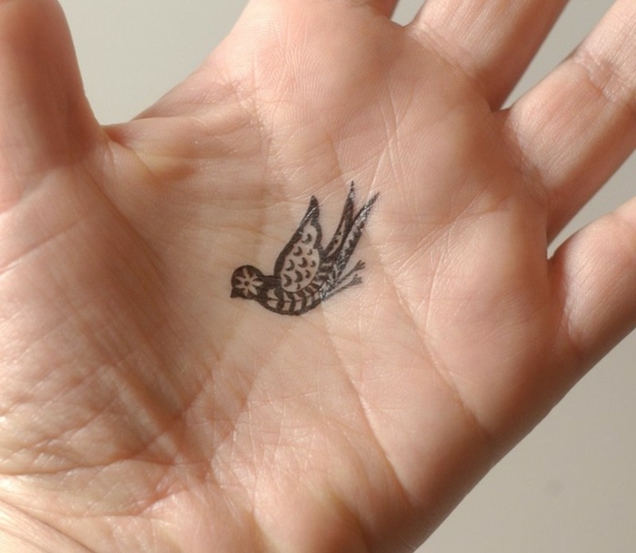 Winziges Vogel Tattoo an der Hand, kleine Tattoo Motive für Frauen, Ideen für Hand Tattoos
