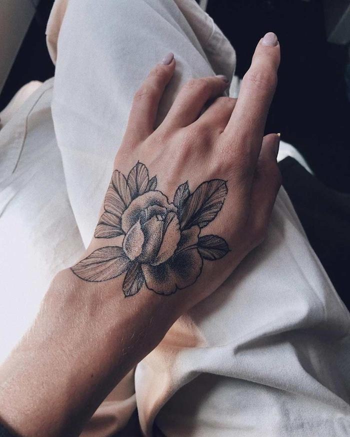 Schöne Tattoos für Frauen, Blumen Tattoo an der Hand, Nagellack in Pastellfarbe, weiße Hose