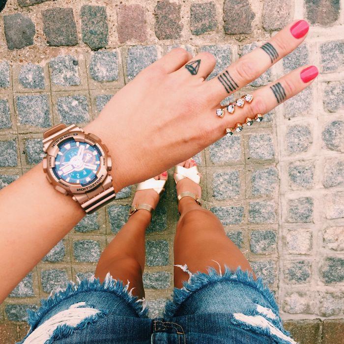 Tattoos an der Hand, kleines Boot am Ringfinger, Striche am Zeigefinger und Mittelfinger, roter Nagellack, zerrissene Denim Shorts