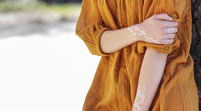 Weiße Henna Tattoos an beiden Armen, kleine Herzen und Blumen, temporäre Tattoos