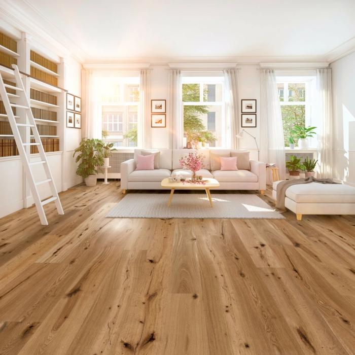 Parkettboden, ein beiger Sofa mit rosa Kissen, grauer Teppich, Holz als natürlicher Baustoff