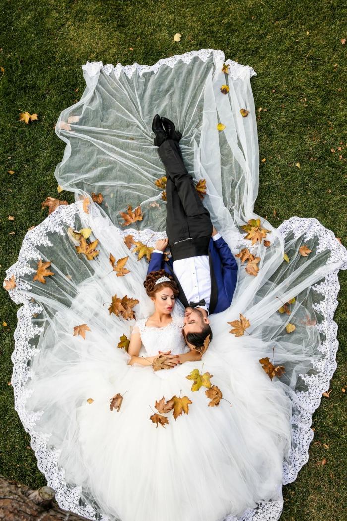 ein prächtiges Brautkleid und ein Bräutigam in blauem Kostüm, Hochzeit im Herbst