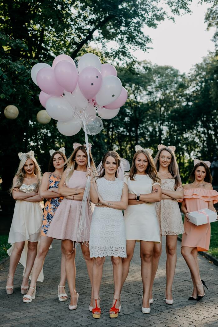 JGA Fotoshooting, eine Reihe von Mädels, die sich auf die Hochzeit vorbereiten, weiße und rosa Kleider