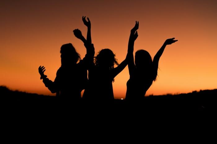 Silhouette von drei Mädchen, die JGA Fotoshooting bei Sonnenuntergang feiern