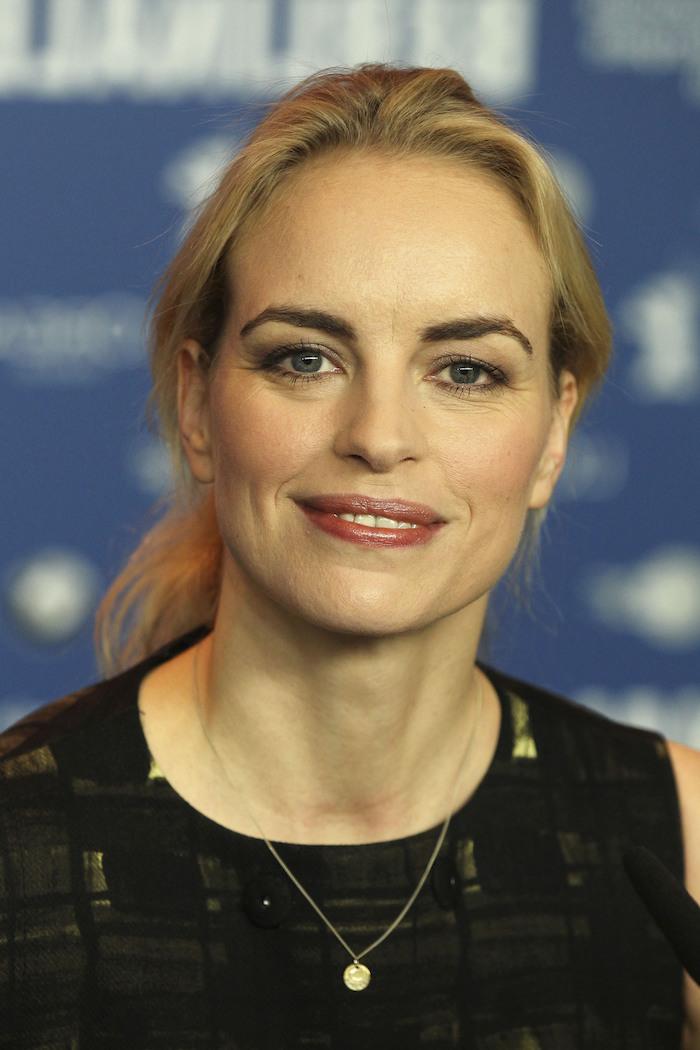 die deutsche schauspielerin nina hoss, eine frau mit goldener Halskette und mit roten lippen und blondem haar