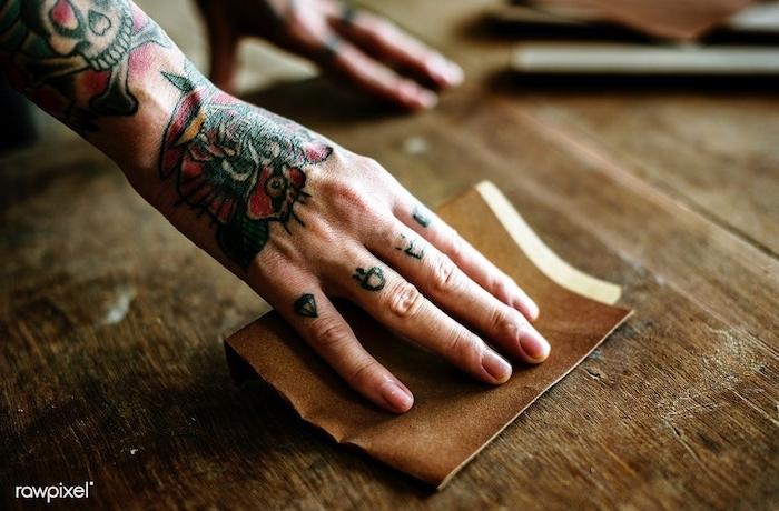 Winzige Tattoos an allen Fingern, Diamant am kleinen Finger, Tasse Kaffee am Ringfinger, Krone am Mittelfinger