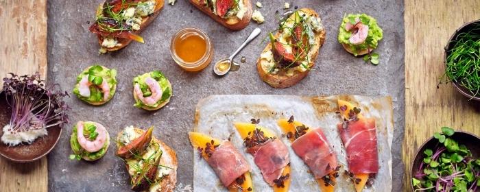 kleine snacks ideen, crackers mit avocaopüree und lachs, papaya mit prociutto und samen, honig