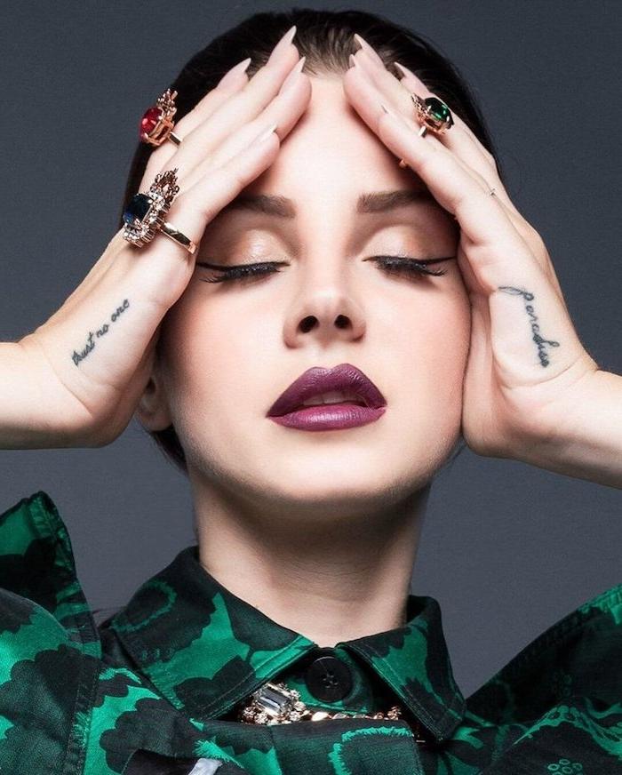 Lana Del Rey Hand Tattoos, Ringe mit großen Steinen, lila Lippenstift und schwarzer Eyeliner, Hemd in Grün Nuancen