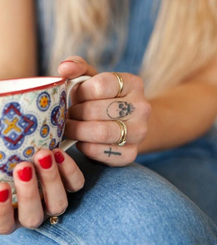 Totenkopf und Kreuz Tattoo am kleinen Finger und Mittelfinger, goldene Ringe, roter Nagellack