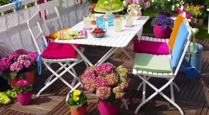 rosarote deko balkon, balkonmöbel weiß mit bunten kissen und blumen rund herum