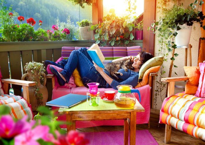 obi terrassenplaner, eine frau liegt am doppelsofa auf dem balkon und liest zeitung, katze kuscheln, rosarote deko