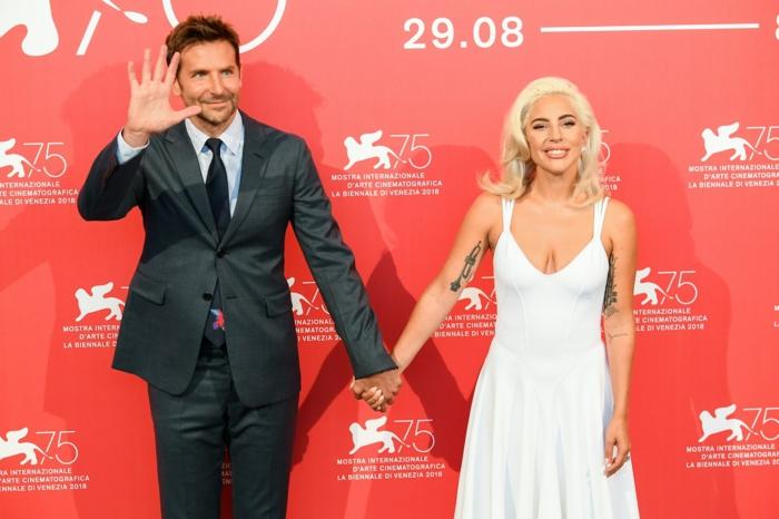 Lady Gaga und Bradley Cooper bei einer Show auf einem roten Hintergrund