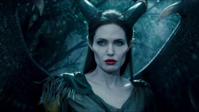 Maleficent hat zwei Hörner und breite Flügel, sie trägt ein schwarzes Kleid und roter Lippenstift