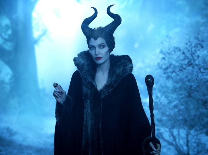 Maleficent trägt ein schwarzer Mantel in einem Wald, sie hat zwei spitze Hörner