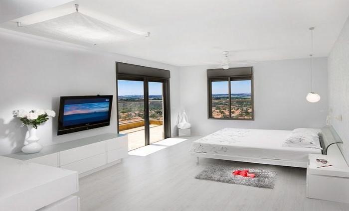 minimalistisch leben, schlafzimmer in simplem weißen design, ein doppelbett, fenster, fernseher