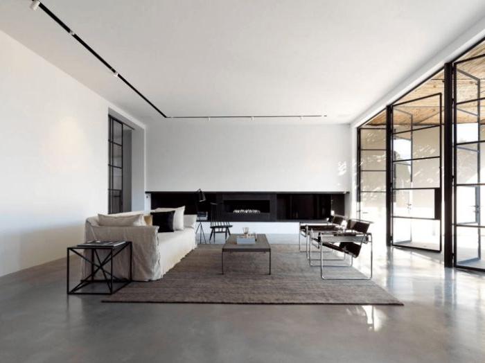 minimalismus tipps, groér grauer raum mit viel natürlichem licht, ein teppich im mittelpunkt des zimmers