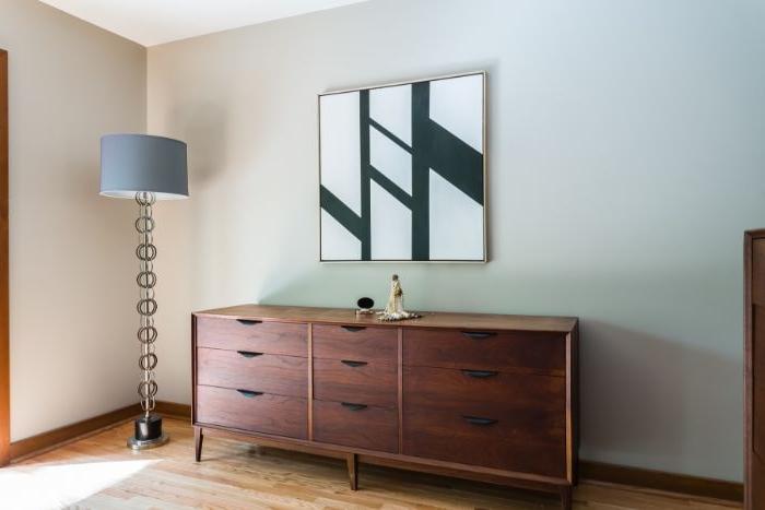 minimalistische bilder, spiegel an der wand angehängt, brauner kleiner schrank, stehlampe