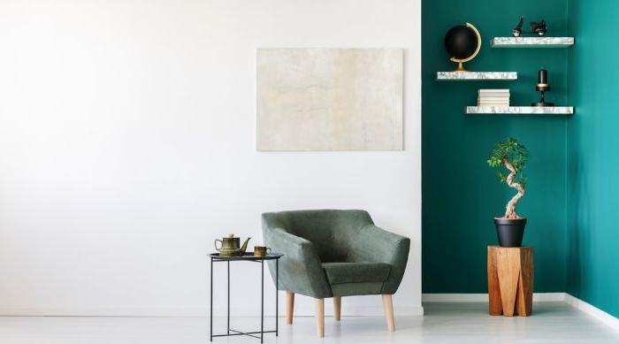 minimalistische einrichtung, minimalismus zu hause, eine petrol türkis farbe wand mit deko und petrol farbe sessel