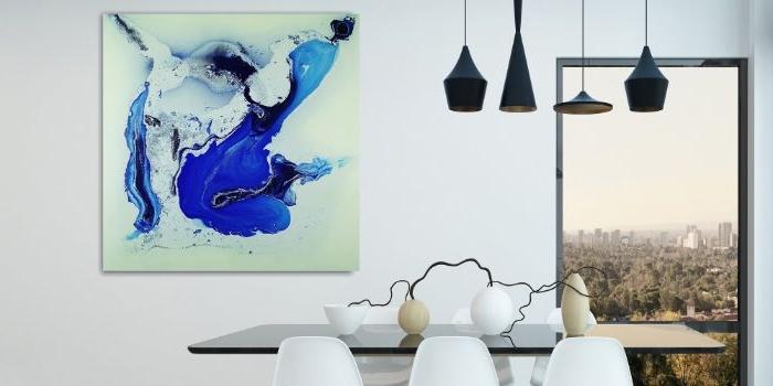 minimalistisch wohnen, essbereich mit einem braunen tisch, weiße stühle, drei vasen als deko, fenster und ein wandbild mit blau