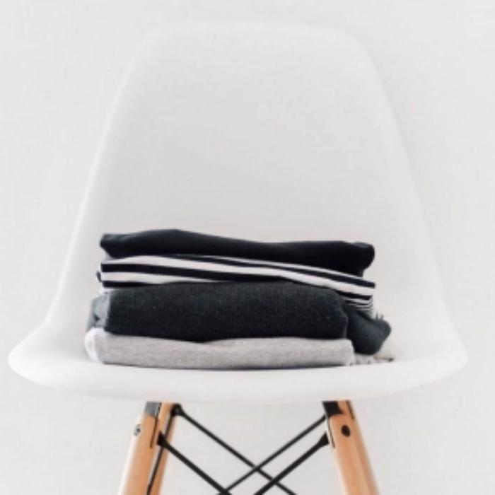 ausmisten minimalismus, ein weißer stuhl mit kleidung darauf, schöne dekor ideen zu hause
