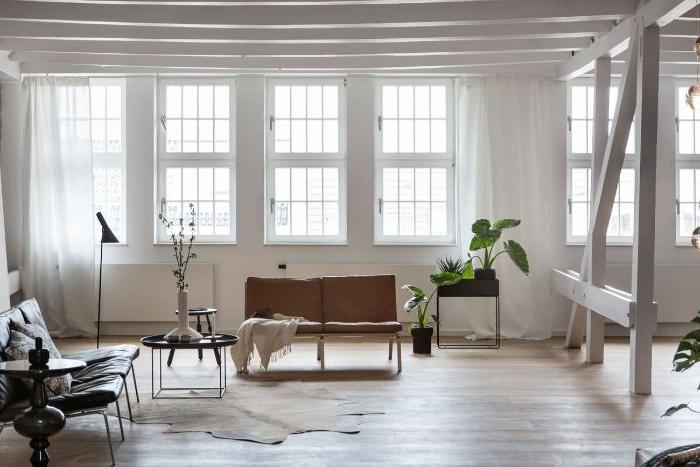 minimalistische einrichtung, wenige dekoelemente, weißes zimmer, braunes doppelsofa
