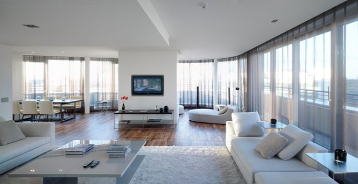 minimalistische möbel, großes wohnzimmer mit einer wand im mittelpunkt, fernseher, sofa mit kissen