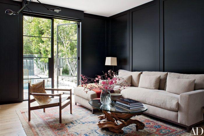 minimalistisch leben erfahrungen, scksofa, ein sofa mit liegesessel, runder tisch mit blumen darauf, sessel, schwarze wand