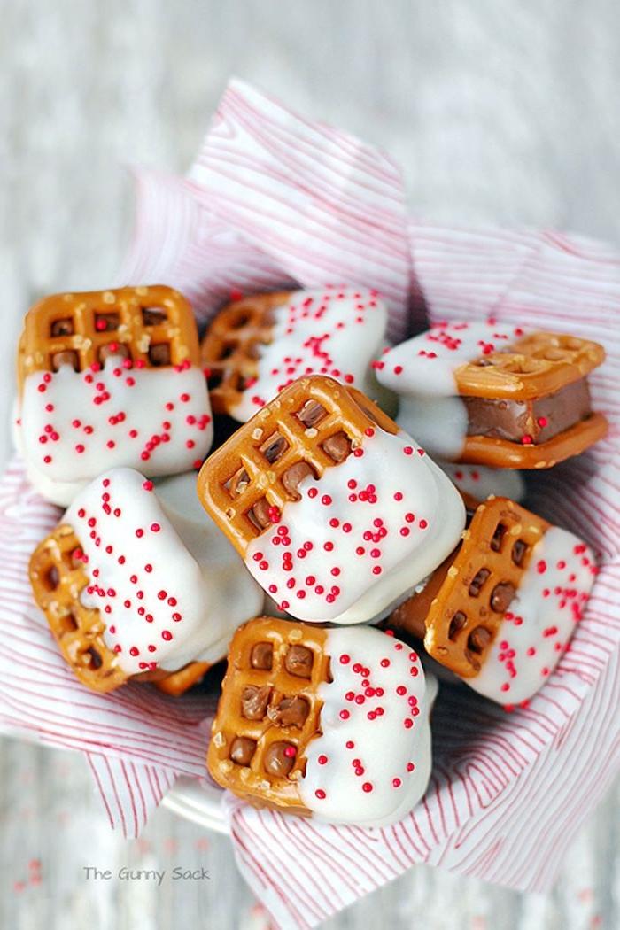Mini Brezeln mit weißer Schokolade und roten Zuckerperlen, leckere Snacks für Party