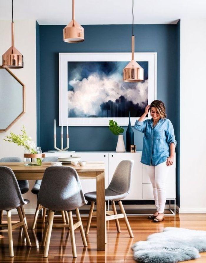 petrol farbe kombinieren, eine frau steht im wohnbereich, petrolfarbene wand, wanddeko bild blau und weiß