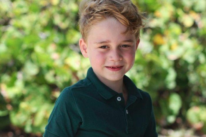 Prinz George ist ein niedlicher Junge mit blonden Haaren und eine grüne Bluse