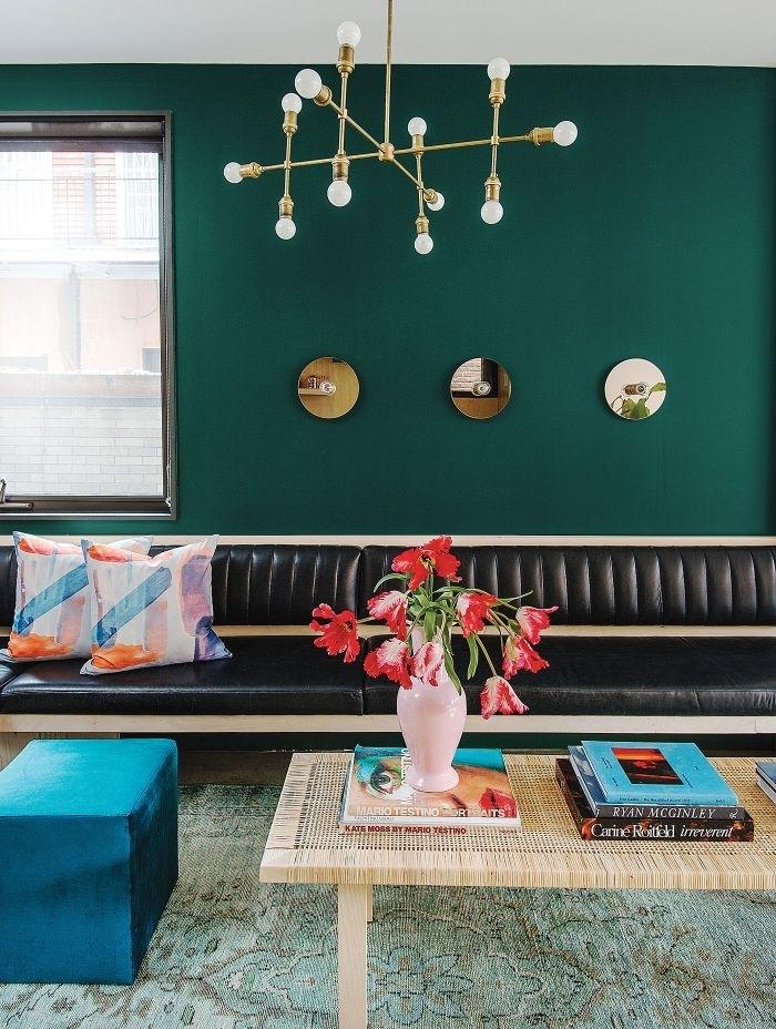 petrol farbe wohnzimmer, dunkle wand, blauer hocker, schwarzes sofa, viel natürliches licht im raum