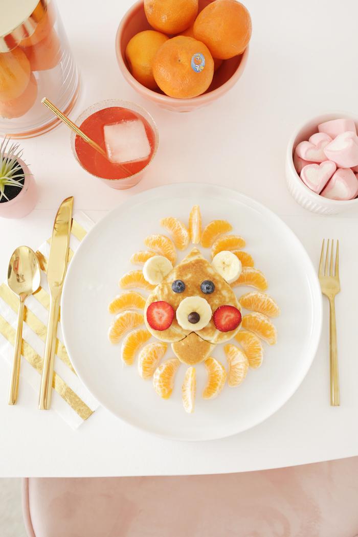 Frühstück für Kinder, Löwe aus Pfannkuchen, Mandarinen für Mähne, Beeren für Augen und Wangen, Bananenscheiben für Ohren