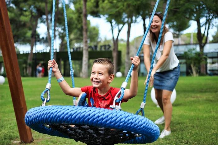 spielplatz für kinder im außenbereich gestalten, spielen im garten, runder blauer schaukel, kleiner junge