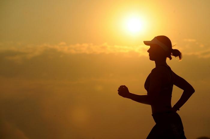 ein Sonnenaufgang und eine Frau, die joggt, schöne Strandfigur