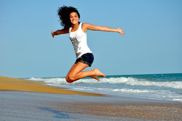 ein schlankes Mädchen springt am Strand, sie hat eine Strandfigur