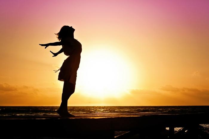 eine Frau am Meer beim Sonnenaufgang, Wasser, Sonne und Strand, Strandfigur