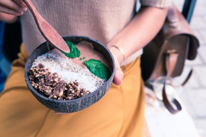 eine Schale mit Superfood, grüne Blätter, Walnüsse, leckeres Essen