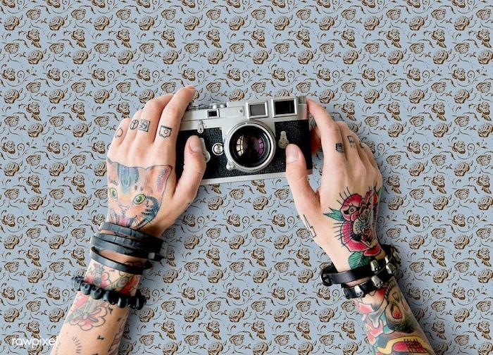 Farbige Tattoos an beiden Armen, Blumen Tattoos und Katze, kleine Tattoo Motive an den Finger, schwarze Armbänder aus Leder, Retro Kamera