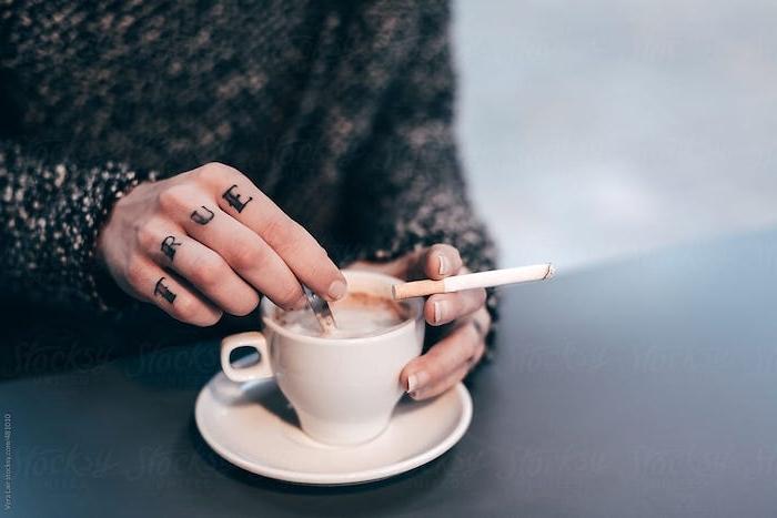 Finger Tattoo an den Fingern, französische Maniküre, Tasse Kaffee und Zigarette