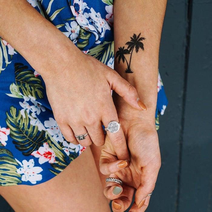 Palmen Tattoo am Handgelenk, dunkelblaues Sommerkleid mit Blumenmuster, silberne Ringe