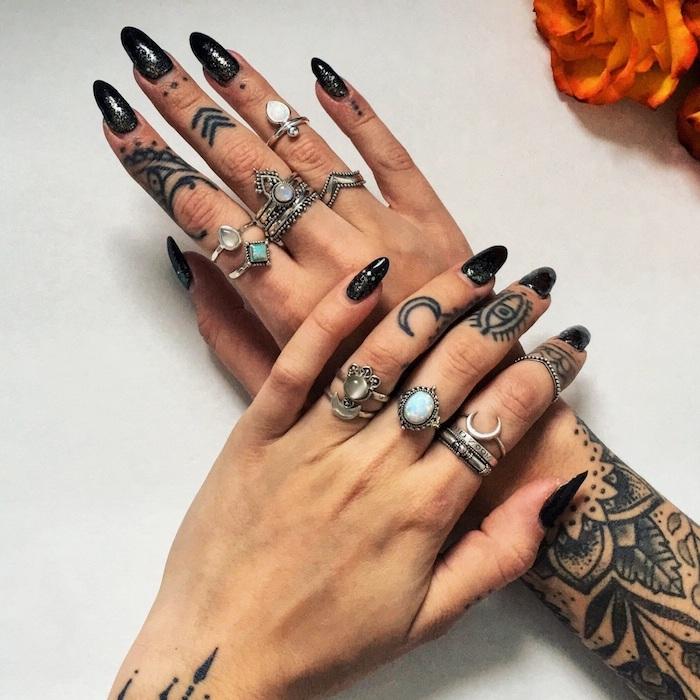Tattoos an jedem Finger und am Arm, schwarzer Nagellack mit Glitzer, silberne Ringe mit Steinen